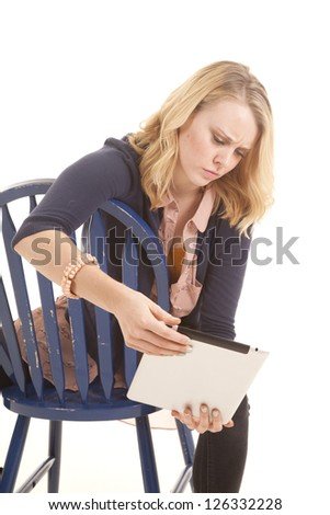 a woman sitting on her chair with a confused expression on her face, while looking at her tablet. - stock photo