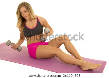 a woman sitting on her fitness mat, with weights working out.