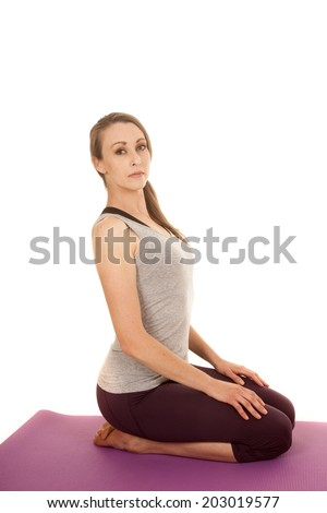 a woman sitting on her knees stretching out her back.
