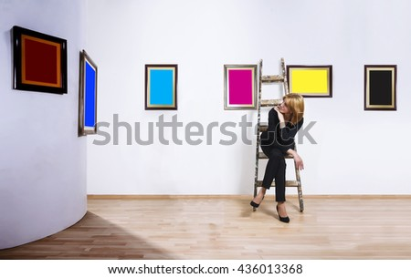 A woman sitting on ladder in gallery and looking at blank of one color frames. - stock photo