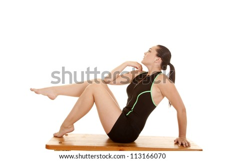 A woman sitting on the bench in her workout clothes with one leg up in the air. - stock photo