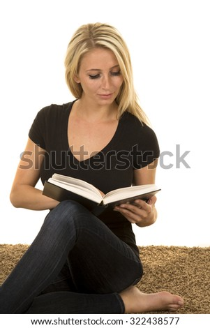 a woman sitting on the carpet reading a book looking down.