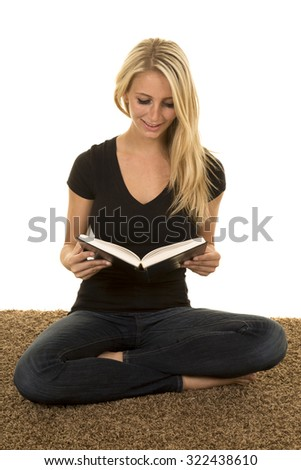 a woman sitting on the carpet reading her book with a smile. - stock photo