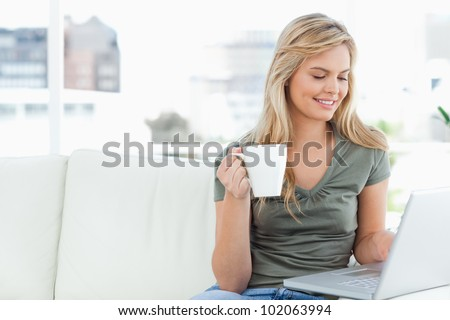 A woman sitting on the couch smiles as she uses her laptop and holds her cup in hand.