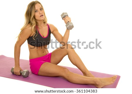 A woman sitting on the exercise mat holding on to her weights.