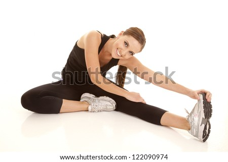 A woman sitting on the floor stretching out her legs with a smile on her face. - stock photo