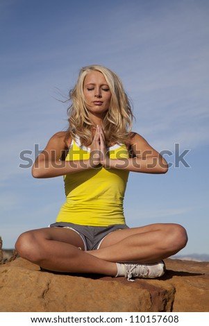 a woman sitting on top of a rock meditating in the outdoors. - stock photo