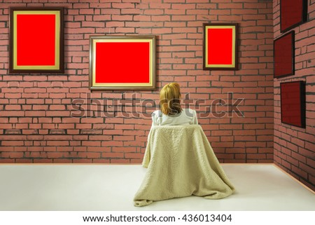 A woman sitting with her back and looking at blank of one red color frames in art gallery. Wall of bricks and frames are painted in red color.