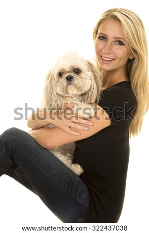 a woman sitting with her puppy on her lap with a smile. - stock photo