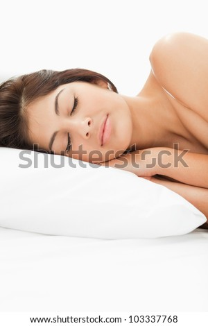 A woman sleeping on the bed with her head resting on the pillow, her eyes are closed and her hands and in between her head and the pillow. A close up photo. - stock photo