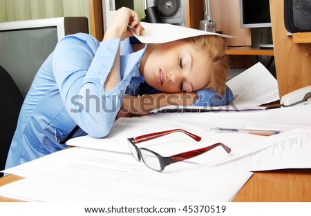 A woman sleeps at her desk - stock photo
