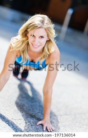 A woman smiles as she prepares to perform a pushup. - stock photo