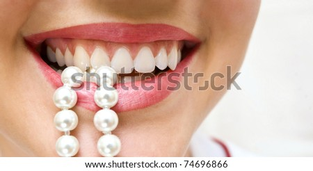 a woman smiles showing white teeth, holding a pearly necklace in to the mouth