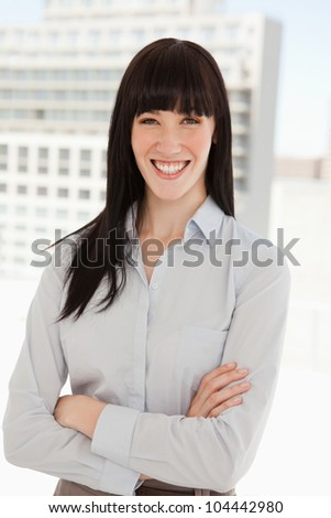 A woman smiling in her office and her arms folded - stock photo