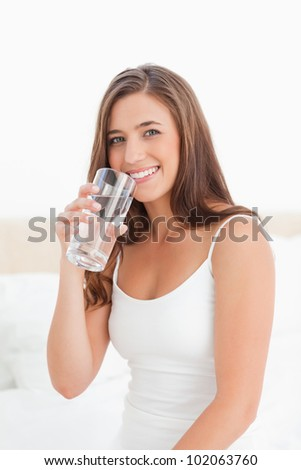 A woman smiling sitting on the bed with a glass of water near her mouth.