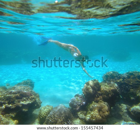 A woman snorkeling in the beautiful coral reef