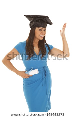 a woman so excited to be graduating.  She is wearing her graduation cap and holding on to her diploma.