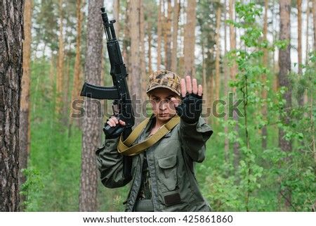 A woman soldier with a weapon shows a hand stop. - stock photo
