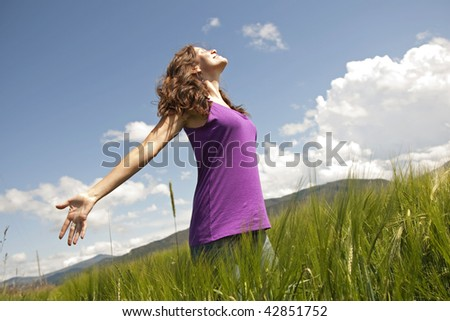 A woman spreads hear arms out of happiness while standing in the green field with blue sky overhead. - stock photo