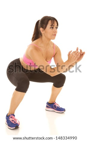 A woman squating and showing her strength by holding this pose - stock photo