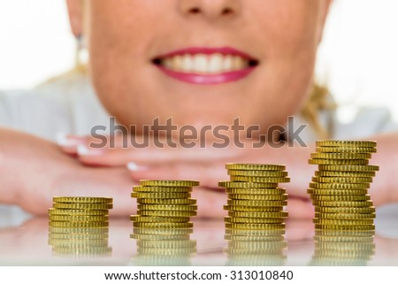 a woman stacking coins. save money for the future.