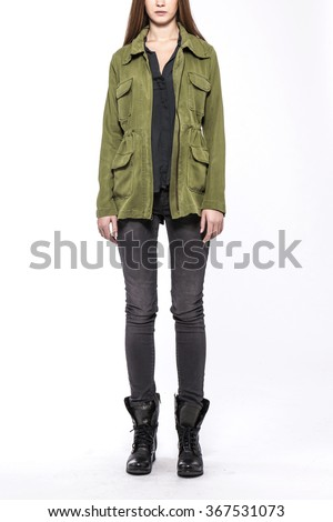 A woman stand up wearing black denim(pants, trousers, jean) and black leather boots and khaki military jacket(jumper) for winter, fall isolated white at the studio.