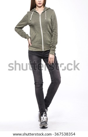 A woman stand up wearing black denim(pants, trousers, jean) and black leather boots and khaki hood t-shirts(top) for fall, sports, jogging isolated white at the studio.  - stock photo