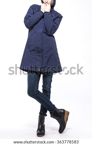 A woman stand up wearing blue denim(pants, trousers, jean) and black leather boots and blue jumper(coat, outer, hood) for winter and sports isolated white at the studio.