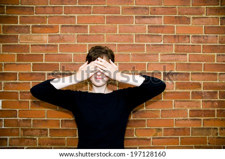 A woman standing against a brick wall and covering her eyes. - stock photo