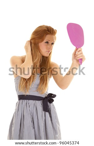 A woman standing an looking in her hand held mirror checking out her hair and make up. - stock photo