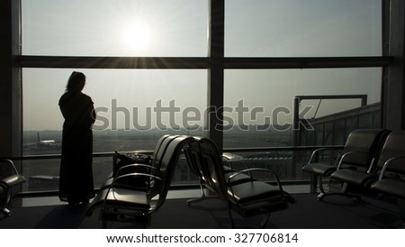 A woman standing at the Airport Window
