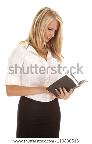 A woman standing holding on to her book reading with a confused expression on her face.