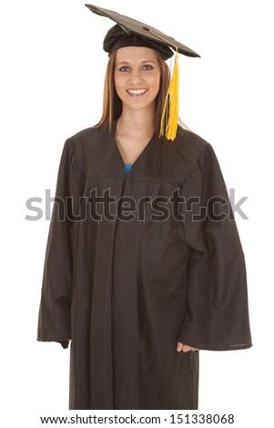 A woman standing in a graduation gown with a smile. - stock photo