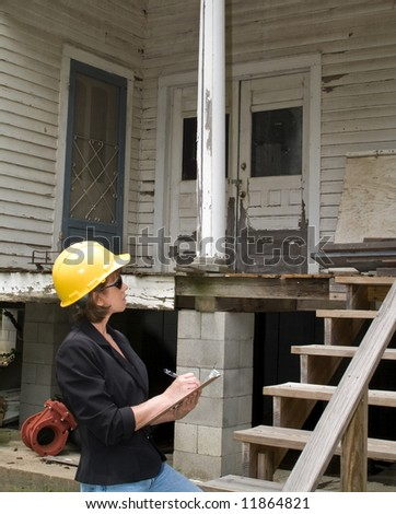 A woman standing in front of an old rundown house, wearing a hard hat and writing on a clipboard.