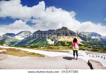 A woman Standing in front of Beautiful Mountain in the Glacier National Park - stock photo
