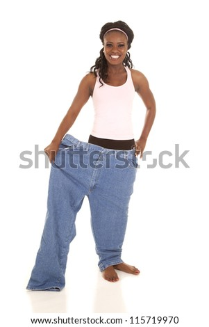 a woman standing in one leg of her pants with a smile on her face. - stock photo
