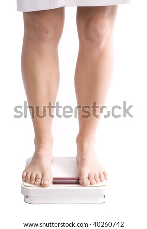 A woman standing on a scale in her white robe. - stock photo