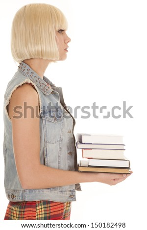 a woman standing sideways holding on to a stack of books with a serious expression on her face. - stock photo