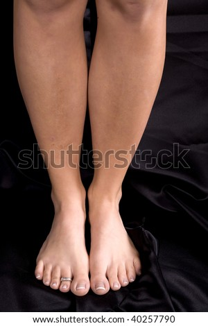 A woman standing tall with legs and feet together on black background.