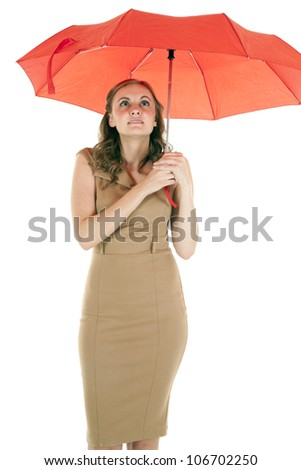 A woman standing under a red umbrella with a small smile on her lips. - stock photo