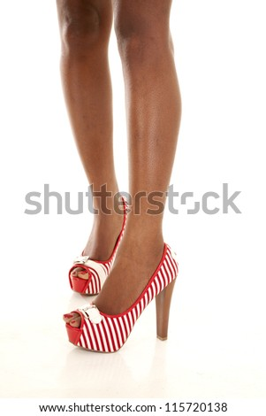 A woman standing up in her red and white shoes showing off her style - stock photo