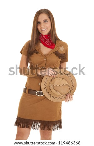 A woman standing with a big smile on her lips in her western costume. - stock photo