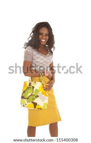 a woman standing with a smile on her face holding on to her colorful purse. - stock photo