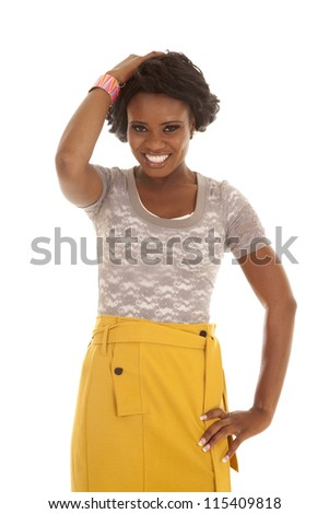 a woman standing with her hands in her hair with a smile on her face, - stock photo