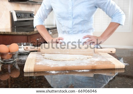 A woman standing with her hands on her hips contemplates the baking she is about to conduct. - stock photo
