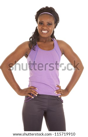 a woman standing with her hands on her hips with a smile on her face. - stock photo