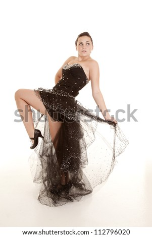A woman standing with her leg up in her black sparkly formal gown. - stock photo