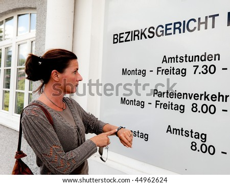 A woman stands before a closed office - stock photo