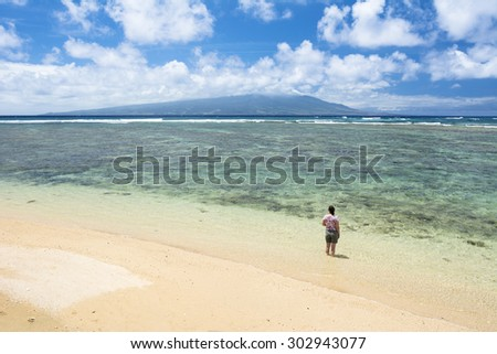 A Woman stands in warm, tropical water on a beach in Molokai Hawaii.