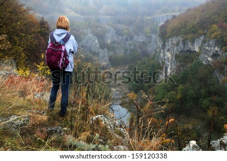 A woman stands on the edge of Emen canyon in Bulgaria on a raw foggy morning in the fall - stock photo
